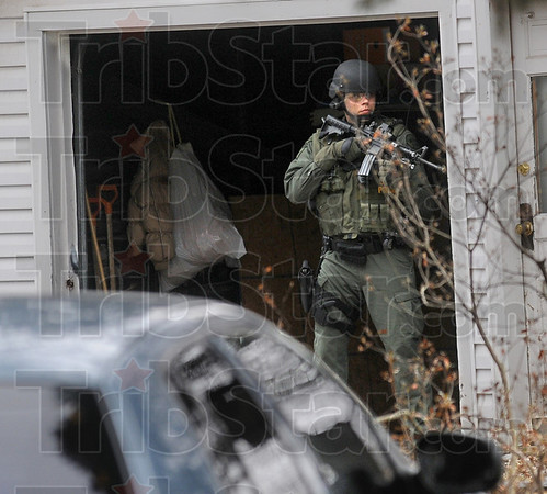 On guard: A member of the Indiana State Police special response team takes cover just inside a garage door as he watches for any movement from a home near 22nd and Poplar Wednesday afternoon.