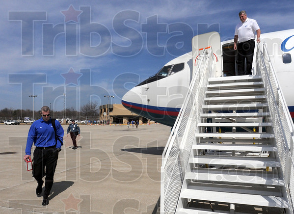 Let's go: Indiana State University athletic director Ron Prettyman waits at the top of the stairs for coach Greg Lansing as they board the aircraft for the trip to Cleveland Wednesday afternoon.