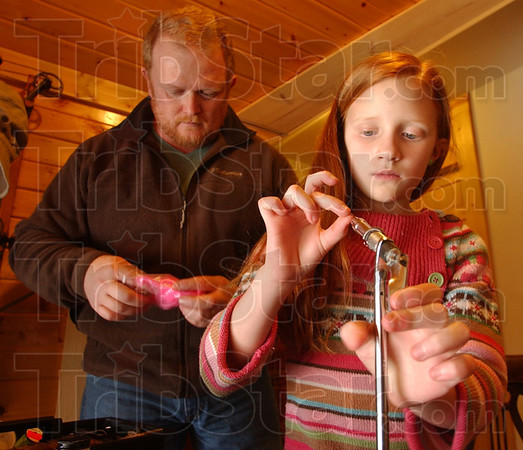Preferences: Steve Joseph pulls pink(his daughter's favorite color) marabou feather from a bag for Grace as she sets a new hook in the vise.