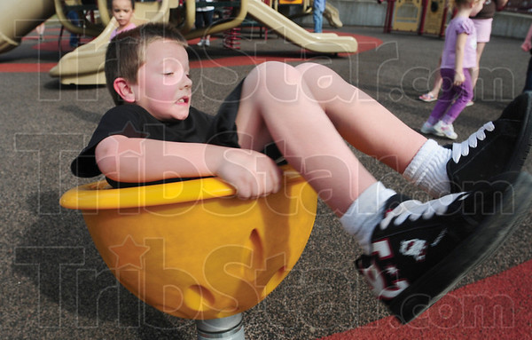 Tribune-Star/Rachel Keyes<br /> Out of control: Eight-year-old Apache Maybaugh spins out of control as he plays on the playground at Deming Park.
