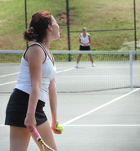 A member of the Falcon squad serves to GWU's Ioana Oprea.