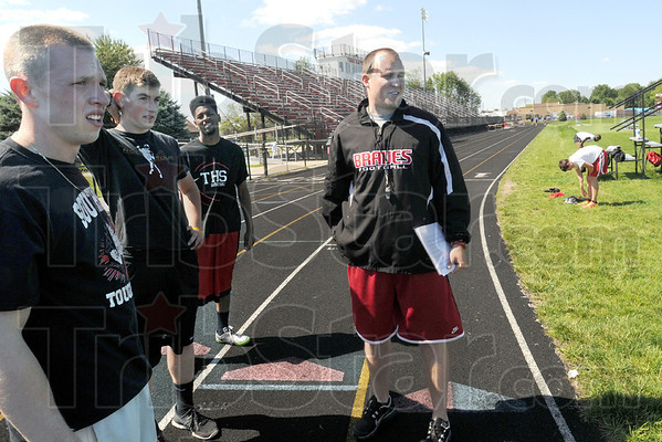 Football/track: Coach Mark Raetz watches his track team prepare for sectionals Monday evening. Several of his track team members also play football. About 30 football players also participate in track and field.