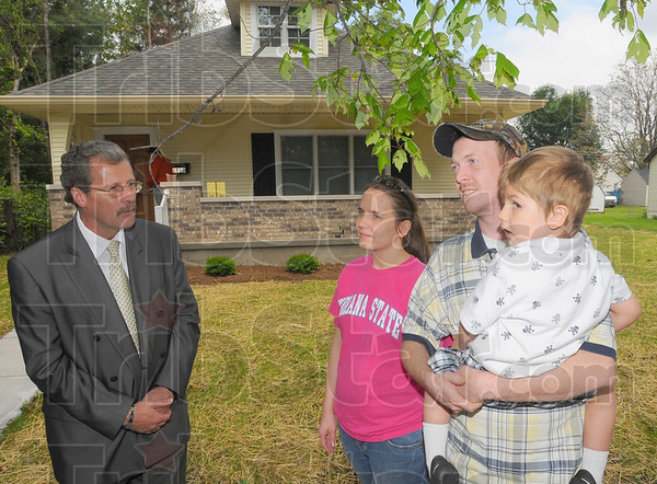 Tribune-Star/Jim Avelis<br /> Coming home: Tim Fagg, director of Light House Mission Ministries, talks with Jackie Nevis and Stephen and Cayden Hecklesberg just prior to the ribbon cutting ceremony of the families' new home on Eagle street Thursday afternoon.