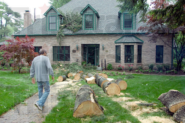 Just finished: Bill Dunbar walks up the walkway of his home located at 9th and Barbour checking for damage on his property. The home was recently finished after seven months of construction. The property suffered damage to the roof and a dormer window along with damage to several trees.