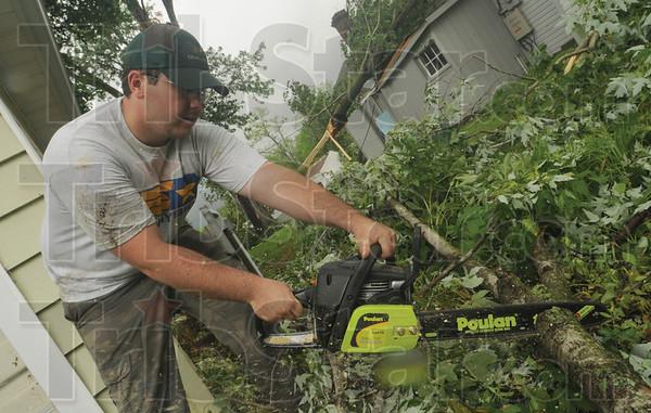 Tribune-Star/Rachel Keyes<br /> Clean up: Jeff Kessinger cut down tree limbs that fell across his mother's driveway in Bridgeton.