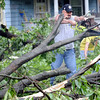 Help: Terry John uses a small chain saw to help remove debris from his brother's north 8th Street home Thursday morning.