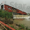 Tribune-Star/Rachel Keyes<br /> Blown away: Pieces of the Bridgeton Bridge lay in the creek below after Wednesday's storm.