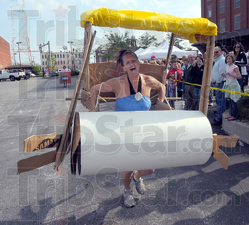 """Tribune-Star/Jim Avelis<br /> Pitter patter: Tonya Pfaff powers her Flintstone mobile across the finish line at the mini Terre Haute 500. The Pfaff family entry took home the prize for """"Most Creative"""" entry."""