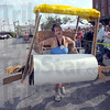 "Tribune-Star/Jim Avelis<br /> Pitter patter: Tonya Pfaff powers her Flintstone mobile across the finish line at the mini Terre Haute 500. The Pfaff family entry took home the prize for ""Most Creative"" entry."