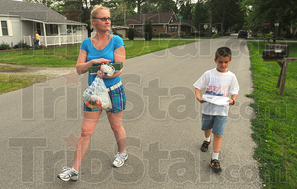Tribune-Star/Jim Avelis<br /> Raising awareness: Gail Phillips and Sebastian Moats canvass the Terre Town neighborhood along Spang street Wednesday evening. They as well as other volunteers placed flyers in newspaper tubes and doors.
