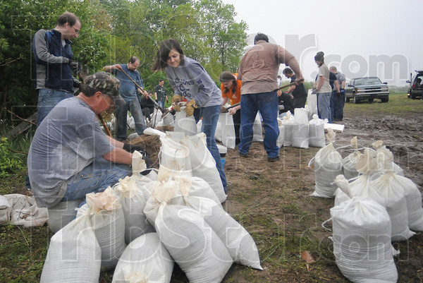 Tribune-Star/Rachel Keyes<br /> Lending a hand: Over 40 volunteers from the Prairieton community, Terre Haute Ministries and the Vigo County Red Cross fill sand bags to put on the Prairieton Levy.