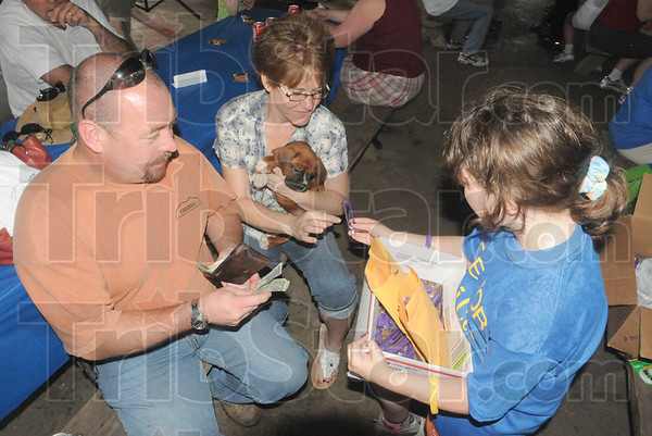 Tribune-Star/Rachel Keyes<br /> Doing my part: Eight-year-old Marjorie Abrell (right) sells a bracelet to Jamie and Darrel Bozarth to raise money for  Cystic Fibrosis research.