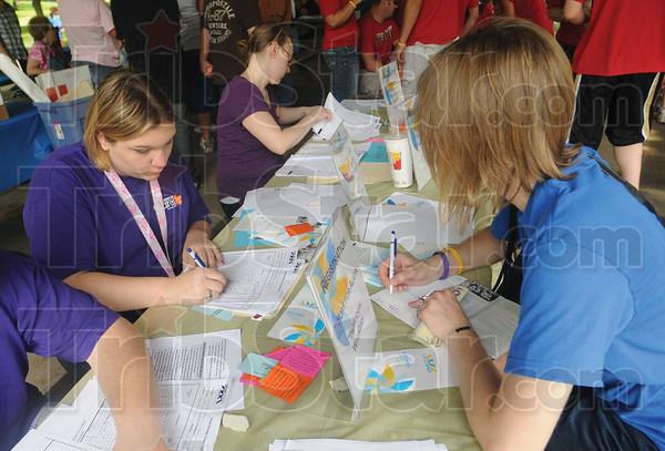 Tribune-Star/Rachel Keyes<br /> Sign me up: Volunteer Alivia Vaillancourt (left) registers Kate Gregg (left) and her team for the Great Strides Cystic Fibrosis Walk.