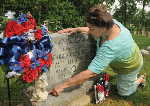 Tribune-Star/Rachel Keyes<br /> Giving honor: Bonnie Butler places flowers on her father Pat Ellinger's grave in honor of memorial day.