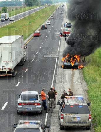 Roasted: Clay County Sheriff's deputies stand-by helplessly as a vehicle burns along the eastbound lane of I-70 Friday afternoon.