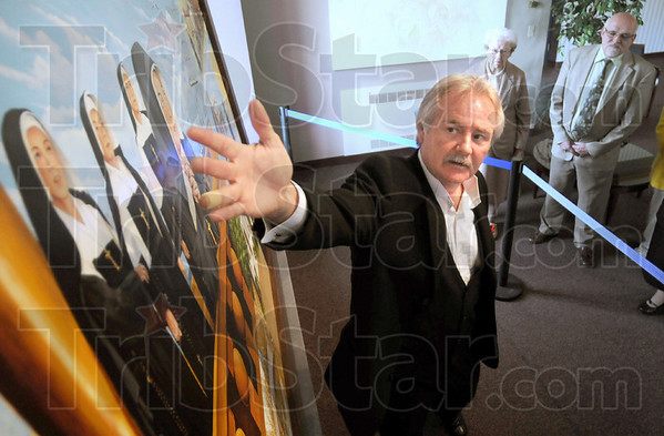 Unveiling: Artist Bill Wolfe unveils his mural at Providence Center Friday afternoon. The artwork will hang in the Vigo County Courthouse.
