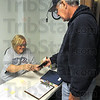 "Voter ID: Poll worker LouAnn Utz checks the identification card of Randy Soules as he prepares to ""early vote"" Saturday morning at the Vigo County Courthouse."