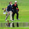 Tribune-Star/Jim Avelis<br /> Reflections: Terre Haute North golfer Sam Pollock walks with Center Groves' Chris Johnson past one of the many puddles left over from heavy overnight rains.