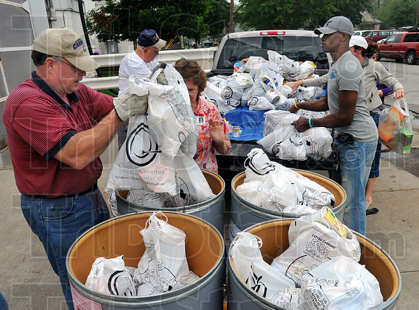 Tribune-Star/Jim Avelis<br /> Helping hands: Bill Haley, left and Jerome Robinson, right, with other volunteers unload John Fishers' pickup truck at the Catholic Charities Food Bank.