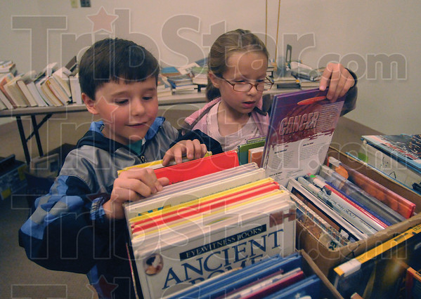 Tribune-Star/Rachel Keyes<br /> Family matters: Kylan Schoffstall (left) and sister Kacie Schoffstal (right) search through the children's section of the annual Friends of the Library book sale.