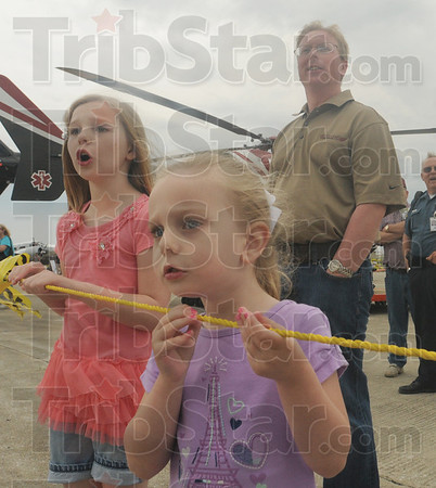 Tribune-Star/Rachel Keyes<br /> Anticipation: Olivia Williams (left) watches with little sister Emily Price (right) as flower bomb is dropped at a target in the Bomb Drop for Cancer  Benefit for Tyler Genneken Foundation at the Hulman Airport Open House.