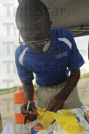 Tribune-Star/Rachel Keyes<br /> Marking the bombs: Indiana State Aviation major Matt Huskey marks the names and number on the bags of flour used for The Bomb Drop for Cancer Benefit for the Tyler Genneken Foundation at the Hulman Airport Open House
