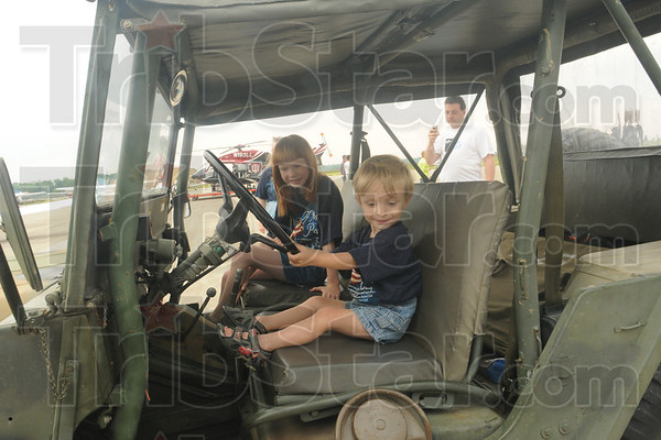 Tribune-Star/Rachel Keyes<br /> Going for a spin: Three-year-old Bendigo James Keegan takes his big sister Carolina Keegan for an imaginary ride it an army jeep at the Hulman Airport Open House Saturday morning.