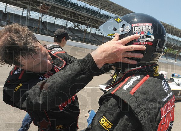 Tribune-Star/Rachel Keyes<br /> Gearing up: Greg Claretto (left) helps his father Joe Claretto with his helmet as Joe prepares to go three laps with one of his racing heroes Mario Andretti.