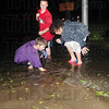 Tribune-Star/Rachel Keyes<br /> Clearing the streets: Eleven-year-olds R.J. Londo (left) Trace Haskin (middle) and Miguel Towles (right) are on a mission to clear the streets of water after the down pour Saturday night. The three are cleaning out the water drains at Poplar and 19th street.