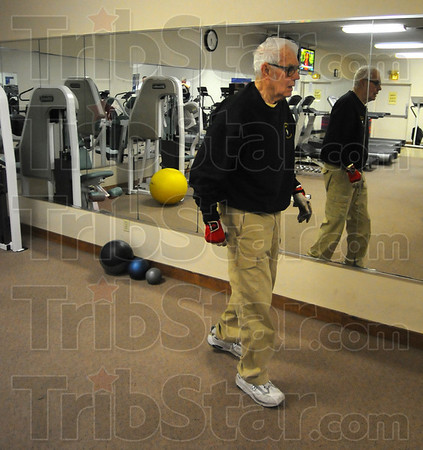 Tribune-Star/Jim Avelis<br /> Still going: Granville Lowe walks with his reflection to the next station during his morning workout routine at Stan's Nautilus.