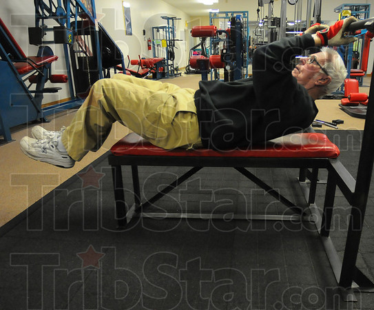 Tribune-Star/Jim Avelis<br /> Crunch time: Before doing weight training, Lowe uses the bench to work his stomach muscles.