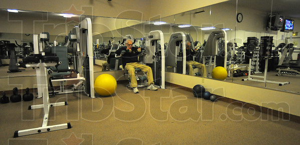 Tribune-Star/Jim Avelis<br /> Quiet time: Granville Lowe quietly works his shoulders and back in a nearly empty weight room just after 5:00 a.m.