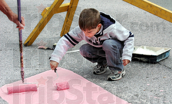 Pink painter: Eight-year-old Eli Storey helps paint the pink ribbon in the intersection of 6th and Wabash Wednesday evening.