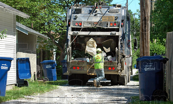 Trashed: A Republic Services worker throws some items in the back of a trash truck in the Collett Park area Monday afternoon.