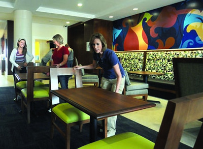Set-up: Amy Isbell (L), Mia Summers and regional manager Trish Williams arrange furniture in the lobby of the Holiday Inn Express Monday afternoon.