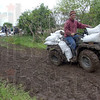 Tribune-Star/Jim Avelis<br /> Slow going: Filled sandbags had to be driven about 3/4 of a mile along the ruttud top of the levee to reach the spot where they were needed. Several local volunteers used their four-wheelers to cart them out, a few at a time.