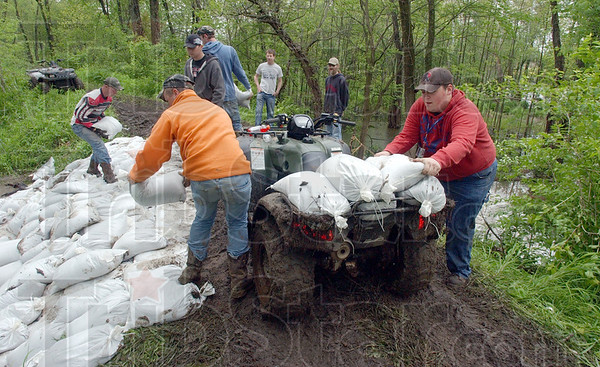 Tribune-Star/Jim Avelis<br /> Many hands: Along the levee near Prairieton volunteers unload another four-wheeler of sandbags to patche the boil in the levee.