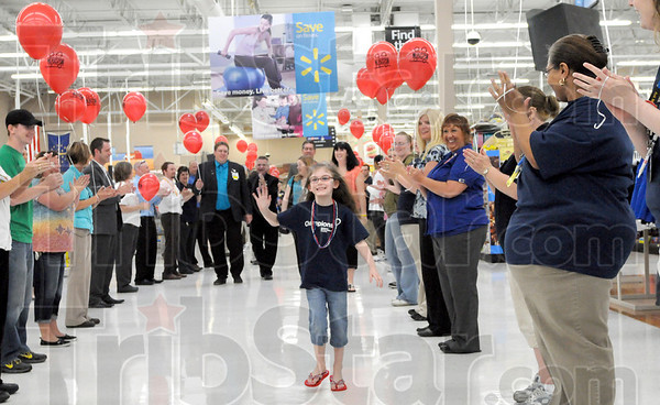 Welcome: Four-year-old Olivia Pierce waves to the welcoming crowd of Walmart employees and associates during her visit to the southside business as a Children's Miracle Network Champion.