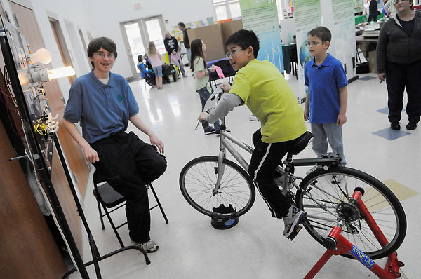 04/09/11   Walker School fourth grader Daren Chen powers a light with his energy through peddling a bike at The District 181 Foundation's  Believe in Green Fair Saturday, April 9th 2011 at Clarendon Hills Middle School. SCARCE volunteer David Knapp, a soph at Wheaton North HS monitors the exhibit.  Scott Hardesty/www.starphotos.us