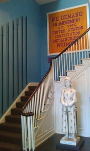 (from left) Poles used by picketing suffragists for banners and self-defense; a reproduction of the Great Demand Banner; and a marble statue of Joan of Arc (Jehanne au Sacre, by Prosper d'Épinay), at the Sewall-Belmont House & Museum (8/20/11)