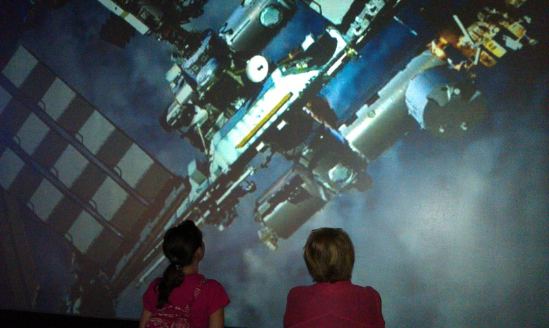 "@KelleyApril inspects a video image of the International Space Station in the Moving Beyond Earth exhibit, with Valerie Neal, curator of the Post-Apollo Human Spaceflight Collection at the Smithsonian's National Air and Space Museum, during a ""tweeunion"" of space tweeps (8/8/11)"
