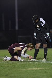 Winthrop's 20, Daniel Di Biagio, ties the shoe of the goalie, number 33, Enrique Miranda.