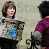 Picture this: Marshall, Illinois photographer Elizabeth McConchie shows some of her photographs to Michelle Shobe and Emilly Tarter at the Martinsville business expo Sunday afternoon.