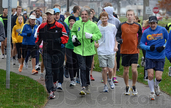 Tribune-Star/Joseph C. Garza<br /> An Olympian in Cross Country Town: Frank Shorter, center, a gold medal winner in the 1972 Olympics, leads a community run at Memorial Stadium Sunday as part of the 2011 NCAA national cross country championship weekend.