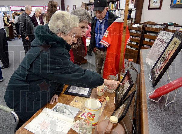 Tribune-Star/Joseph C. Garza<br /> Remembering: Norma Lewis points to a photograph as she and Betty Lewis and Jack Lewis look over one of the displays in The Way We Worked exhibit Sunday at the Marshall, Ill., Public Library.