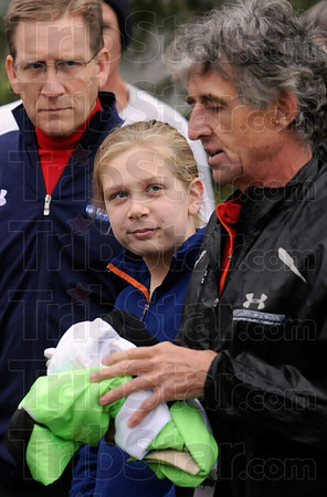 Tribune-Star/Joseph C. Garza<br /> Golden experience: St. Patrick's sixth-grader Maggie Mullican, center, listens as Olympian Frank Shorter, right, discusses his 1972 Olympic experiences before a community run Sunday at Memorial Stadium.