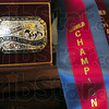 Ribbon: Detail photo of World Championship belt buckle and ribbons won by Dave and Brenda Kellerman.