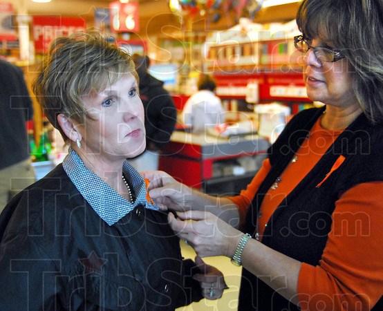 Pinned: Baesler's Market customer Janice Vietta (L) gets an orange ribbon pinned to her blouse by Robin Heng after she donated to the orange ribbon campaign Friday afternoon.