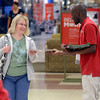 Tribune-Star/Joseph C. Garza<br /> Sales in print: Peggy Hutchins of Bridgeton takes a sales ad from J.C. Penney employee, Abdul Kassim, a Ghana native and Indiana State University student, early Friday morning.
