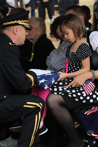 Anyca Miller, the five year-old daughter of Staff Sgt. Chris Newman, is presented with a flag during the military funeral for Newman in Shelby, NC on November 9, 2011. Newman and three other US servicemen were killed in a suicide car bombing October 29 in Kabul, Afghanistan.